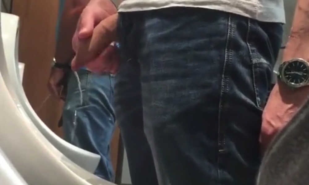uncut guy with lot of foreskin peeing at urinal