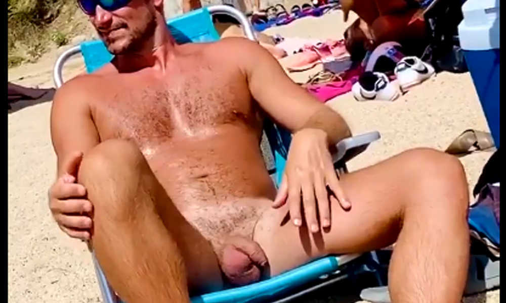 uncut nudist man chilling at the beach