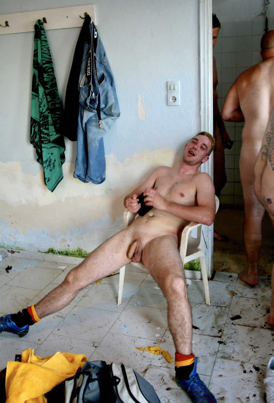 naked guy spreading legs in locker room