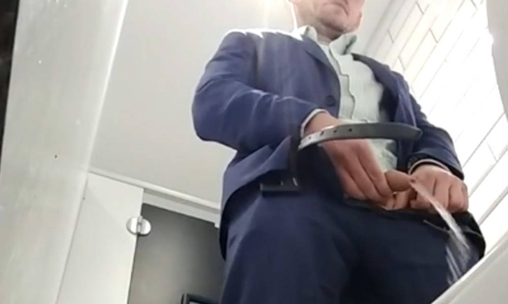 guy in suit caught peeing in public toilet